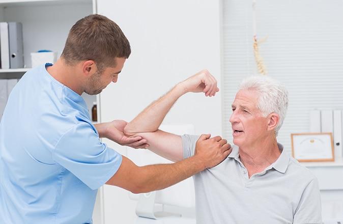 Arts controleert man met symptomen van artrose.