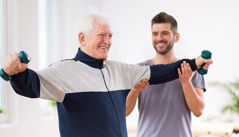 Een oudere man voert oefeningen uit onder begeleiding