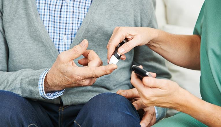 Verpleegkundige meet de bloedsuikers van iemand met diabetes type 2