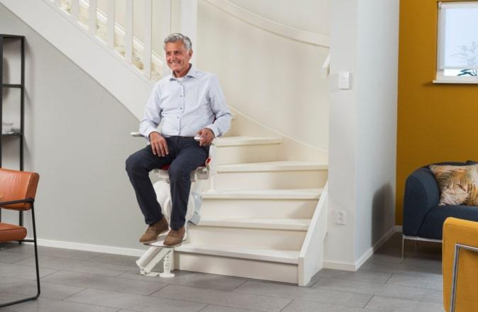 Een man zit op de traplift die hij wil verkopen.