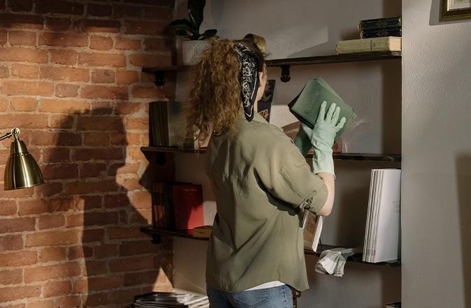 Een hulp in de huishouding helpt met het schoonmaken van de ramen van een oudere.