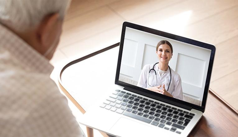 Een oudere man praat dankzij e-health via de laptop met zijn arts.