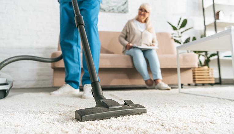 Een thuiszorgmedewerker stofzuigt de woning van een oudere als onderdeel van ouderenzorg aan huis.