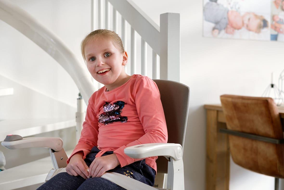 Tara is een meisje van 9, ze zit lachend op haar eigen traplift van Otolift.