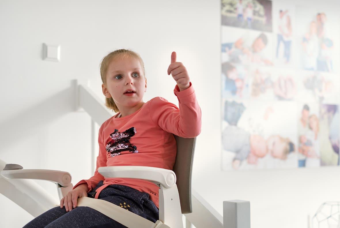 Tara zit op haar traplift. Vanwege haar ziekte kan ze anders niet naar boven.