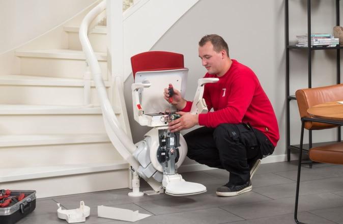 Een monteur van Otolift vervangt traplift accu's die leeg zijn.