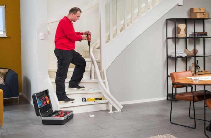 Een monteur van Otolift is een traplift voorzichtig en snel aan het verwijderen.