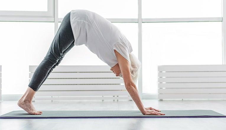 Een oudere vrouw voert oefeningen uit voor meer balans.