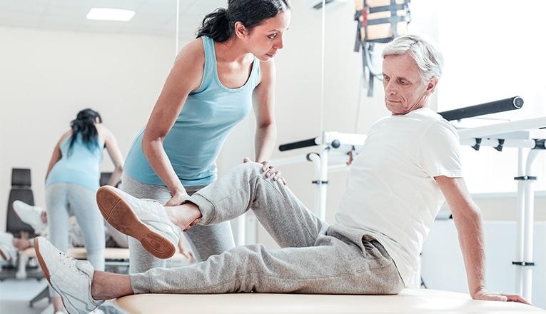 Een fysiotherapeut helpt een man met artrose in zijn knie met zijn oefeningen.