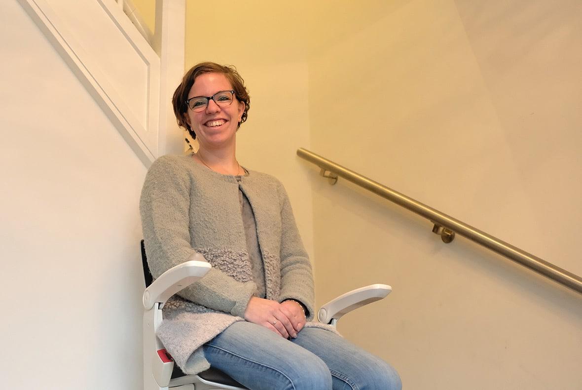 Marianne zit op de traplift die zij van Otolift kreeg