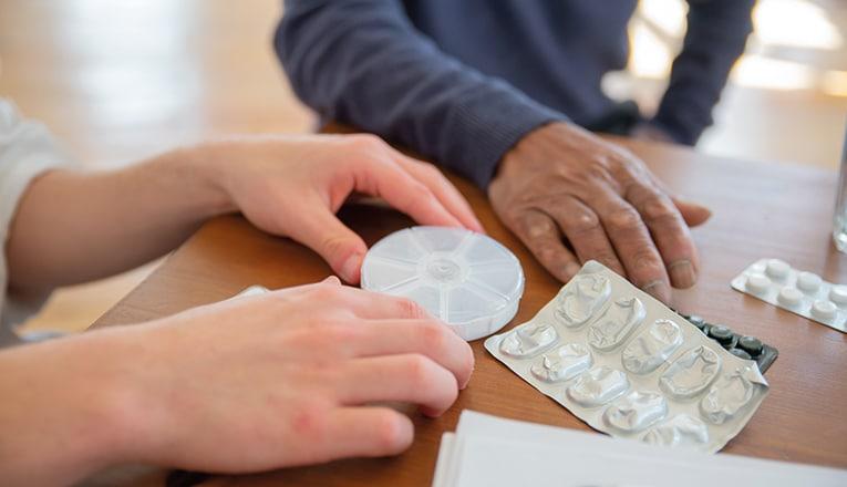 Een hulpverlener geeft een oudere in een verpleeghuis zorg door te helpen met de dagelijkse medicatie.