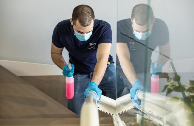 Een medewerker van Otolift maakt de rail van een traplift voorzichtig schoon.
