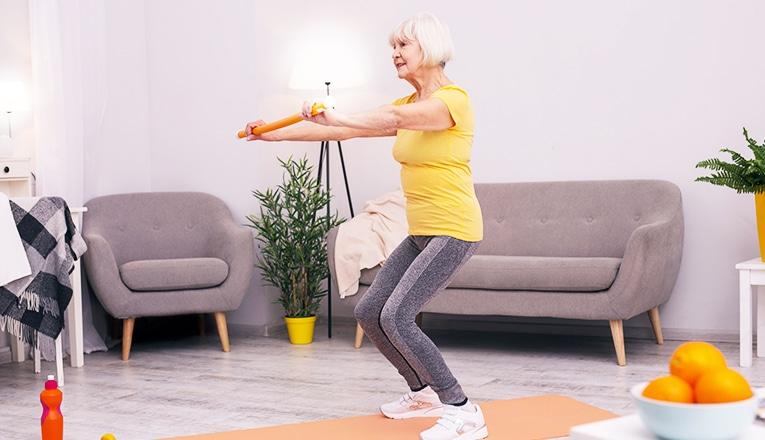 Een oudere vrouw doet squats als fitness oefening.