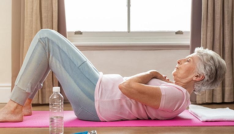 Een oudere vrouw doet sit-ups als fitness oefening.