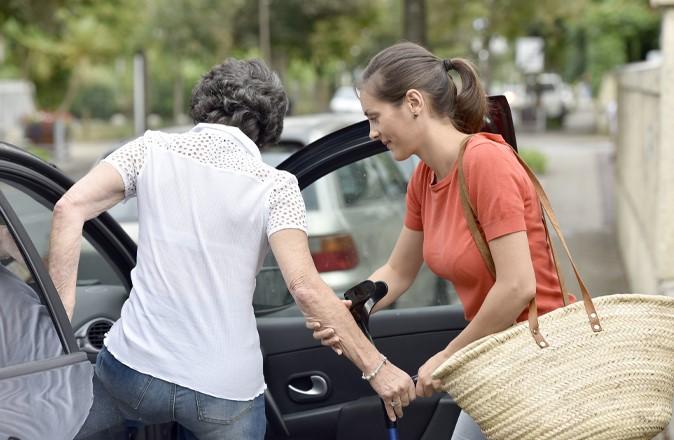 Wat doet een mantelzorger? Deze mantelzorger helpt een mevrouw in de auto te stappen